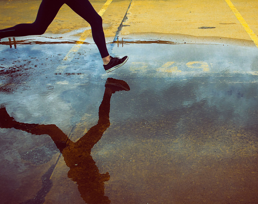 Person running through a puddle.