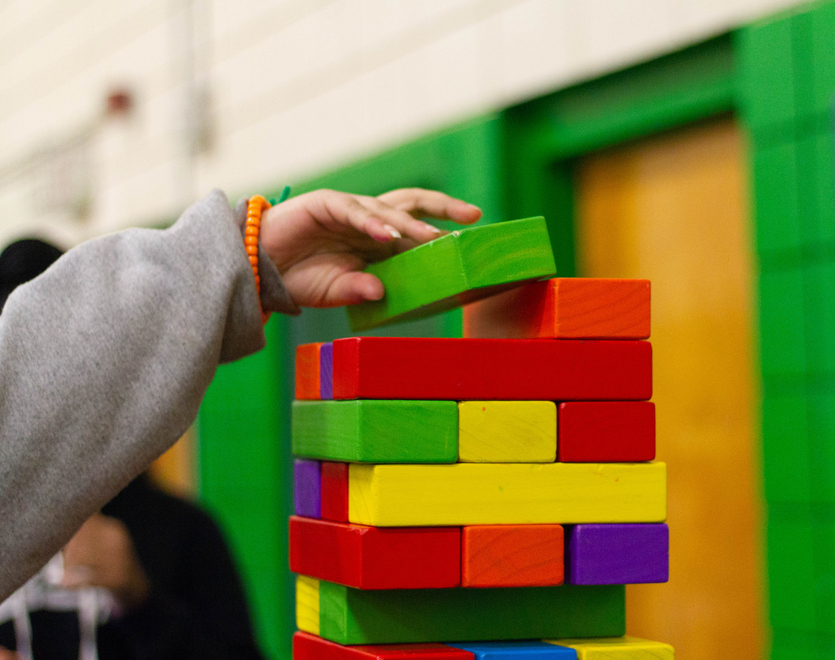 Child playing with wooden, coloured building blocks